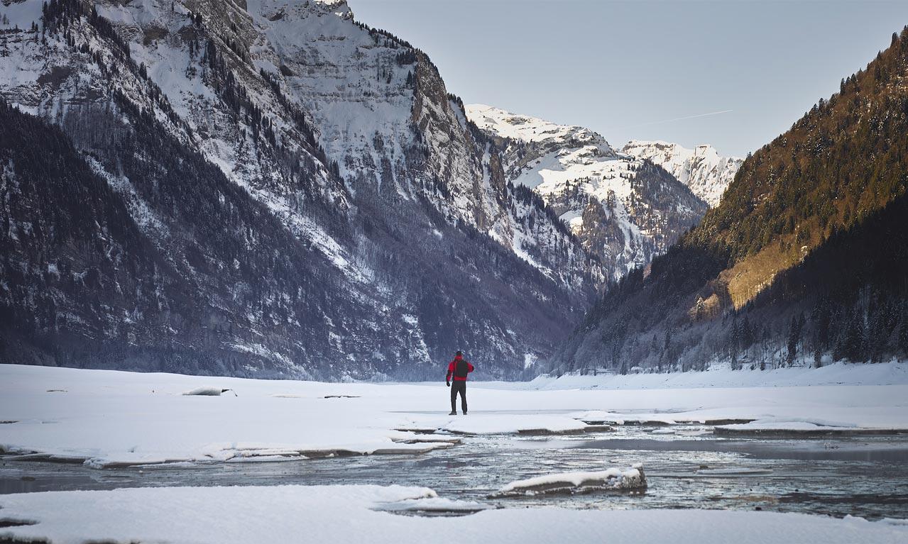 Kloentalersee Mann Rote Jacke Berge gefrorener See Schweiz